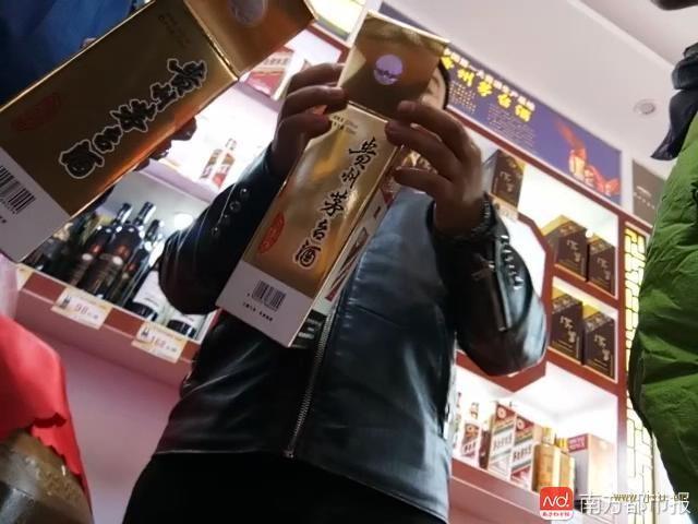茅台镇的酒铺商家,正在跟记者介绍假冒茅台包装的特点.JPG