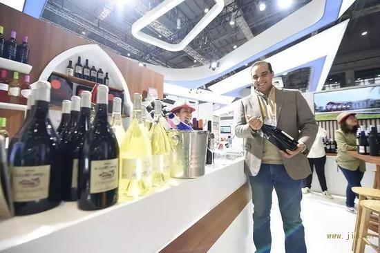 11月7日,在第二届进博会上,摩洛哥红农场酒庄总经理马蒙·萨耶展示红酒。新华社记者尹炣摄