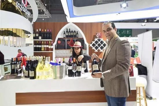 11月7日,在第二届进博会摩洛哥红酒展位,摩洛哥红农场酒庄总经理萨耶展示红酒。新华社记者尹炣摄